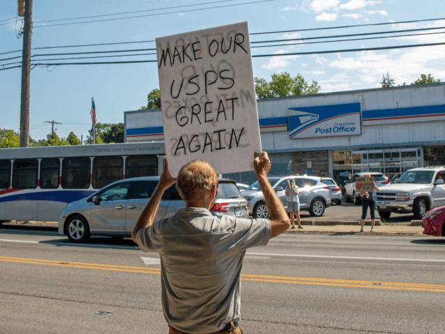 Demonstranten protestieren vor einem Postgebäude.
